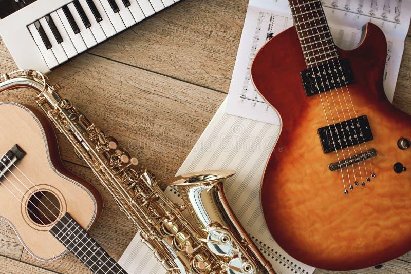 Sammansättning av olika musikinstrument: synt, elektronisk gitarr, saxofon och ukulele som ligger, ark med royaltyfri foto
