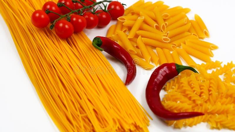 Sammansättning av olika nudlar med peperonin och tomater royaltyfria foton