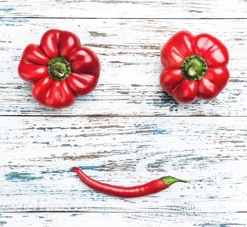 Sammansättning av olika typer av röda peppar, grönsakleende Bästa sikt på gammal vit-blått bakgrund arkivbild