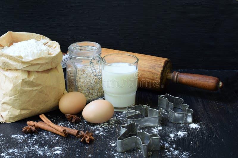 Sammansättning av påsen av vetemjöl, ägg, havre, mjölkar och kavlen Förberedelse för att knåda deg, stekhet kaka på mörk backgro royaltyfri bild
