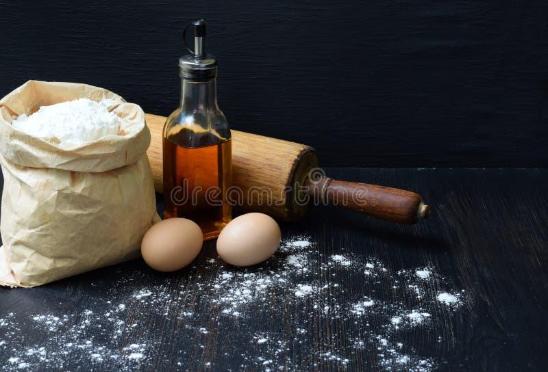 Sammansättning av påsen av vetemjöl, ägg, olja och kavlen Förberedelse för att knåda deg som bakar på mörk bakgrund Utrymme för arkivbilder