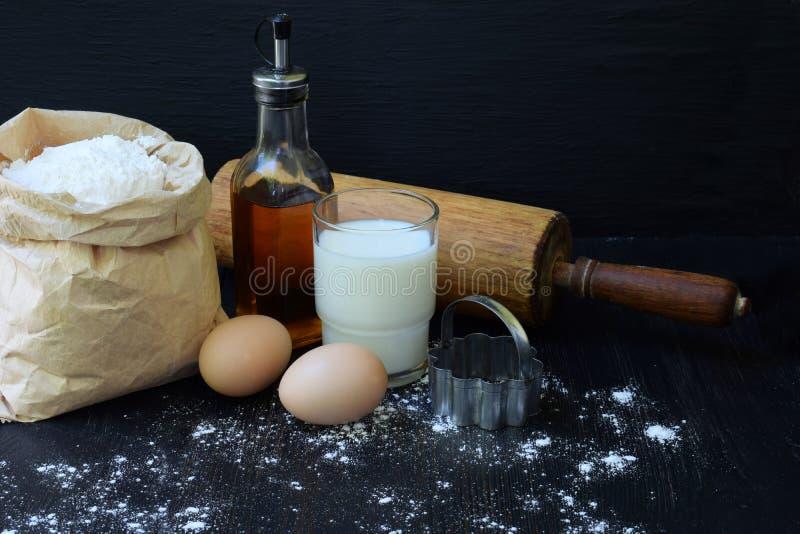 Sammansättning av påsen av vetemjöl, ägg, olja, mjölkar och kavlen Förberedelse för att knåda deg, stekhet kaka på mörk backgrou royaltyfria bilder