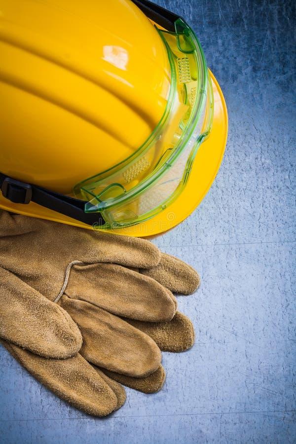 Sammansättning av skyddande läderhandskar gulnar byggnadshjälmen arkivbild