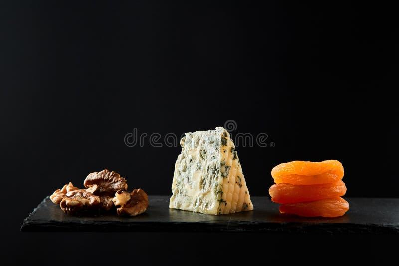 Sammansättning av stycken av valnöten och hårdost och torkad aprikos på svart bakgrund arkivbild