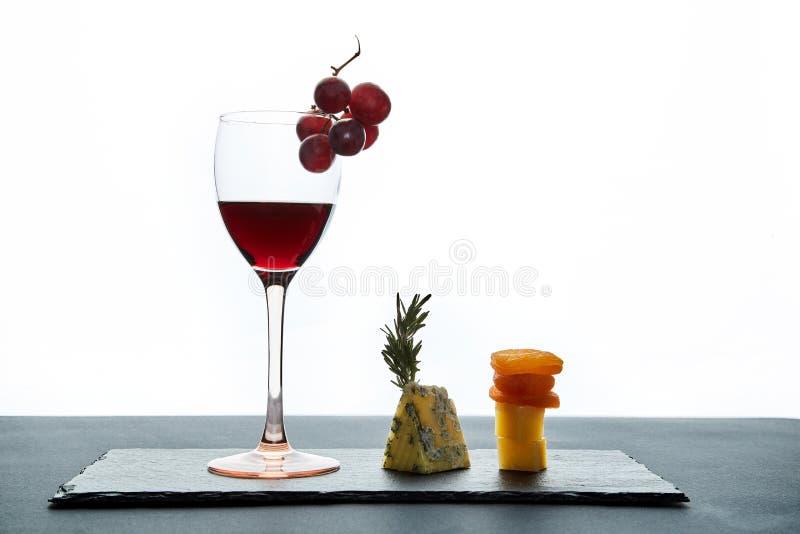 Sammansättning av traditionell aromatisk ost och torkade aprikors med exponeringsglas av rött vin på vit bakgrund royaltyfri fotografi