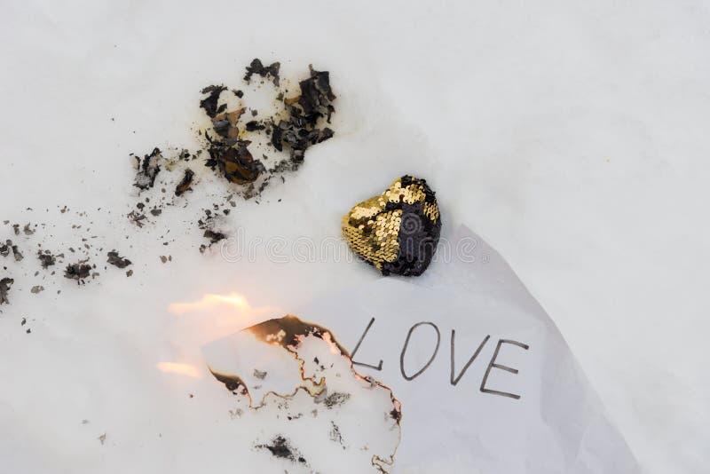 Sammansättning för bruten hjärta Svart och guld- tyghjärta som dekoreras av paljetter som lägger på vit snö nära det pappers- ark arkivbild