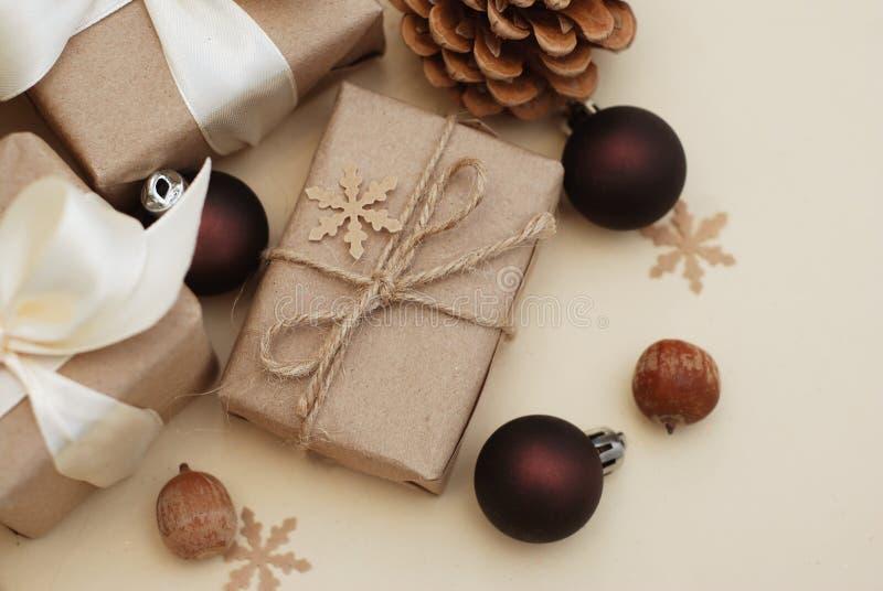 Sammansättning för vinter eller för nytt år eller julmed handgjorda hantverkpappersgåvor med den vita pilbågen på träbakgrund Pin royaltyfri foto