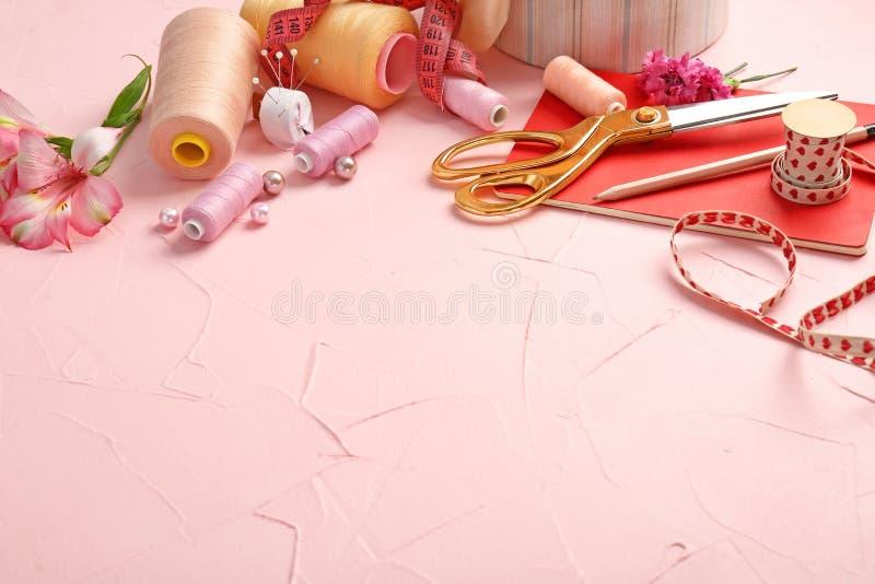 Sammansättning med anteckningsboken, färgtrådar och sytillbehör på färg texturerad bakgrund arkivfoto