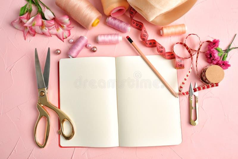 Sammansättning med anteckningsboken, färgtrådar och sytillbehör på färg texturerad bakgrund royaltyfri foto