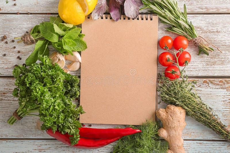 Sammansättning med anteckningsboken, olika nya örter och grönsaker på träbakgrund royaltyfri bild