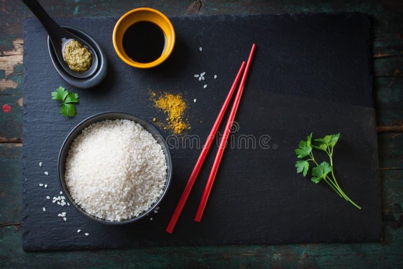 Sammansättning med asiatisk mat - ris för sushi, kryddor, såser och pinnar arkivfoto