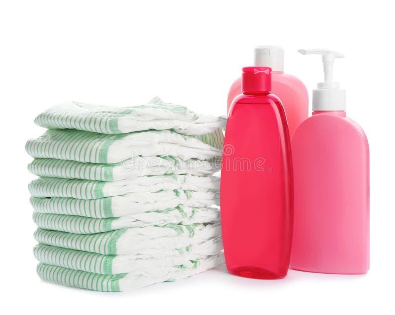 Sammansättning med blöjor och toalettartiklar på vit Behandla som ett barn tillbeh?r royaltyfri fotografi