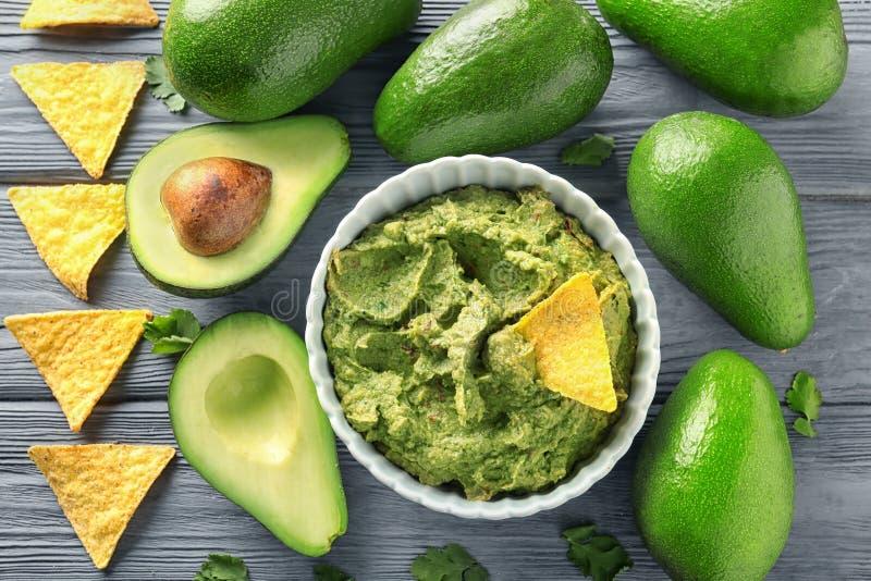 Sammansättning med bunken av läcker guacamole, nachos och mogna avokadon på träbakgrund arkivfoto
