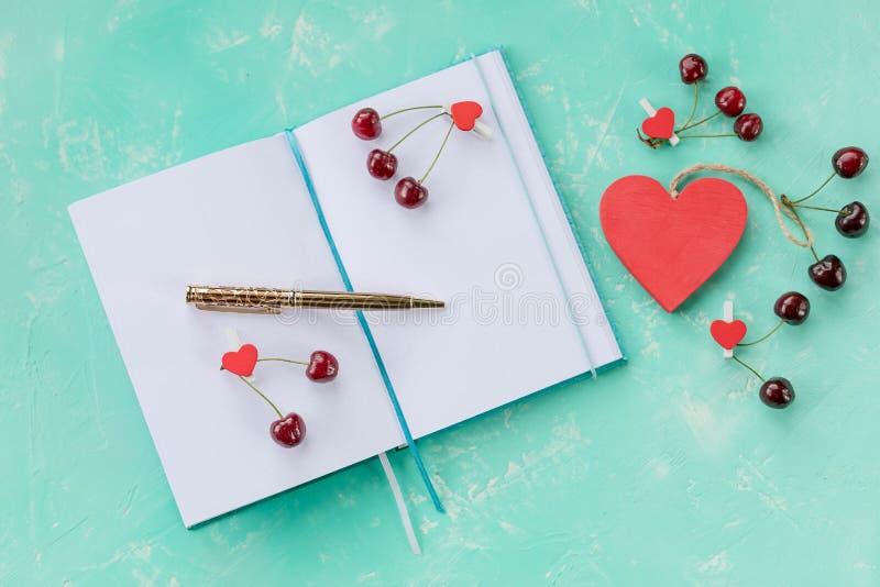 Sammansättning med dagboken och söta körsbär och penna, öppen vitbokanmärkningsbok och dekor med den röda körsbäret, trähjärta på royaltyfria bilder