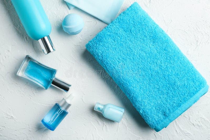 Sammansättning med den rena mjuka handduken och toalettartiklar på vit bakgrund royaltyfria bilder