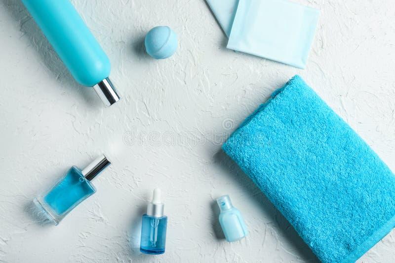 Sammansättning med den rena mjuka handduken och toalettartiklar på vit bakgrund arkivbild
