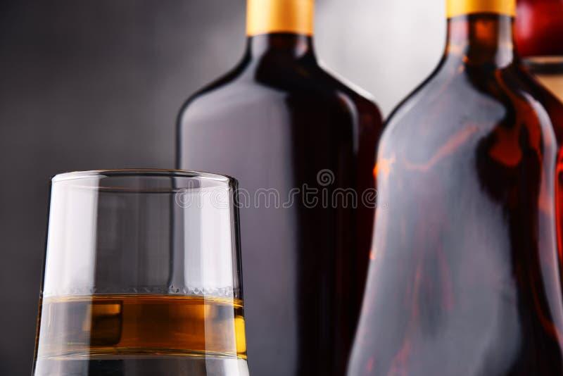 Sammansättning med exponeringsglas och flaskor av hård starksprit arkivfoton