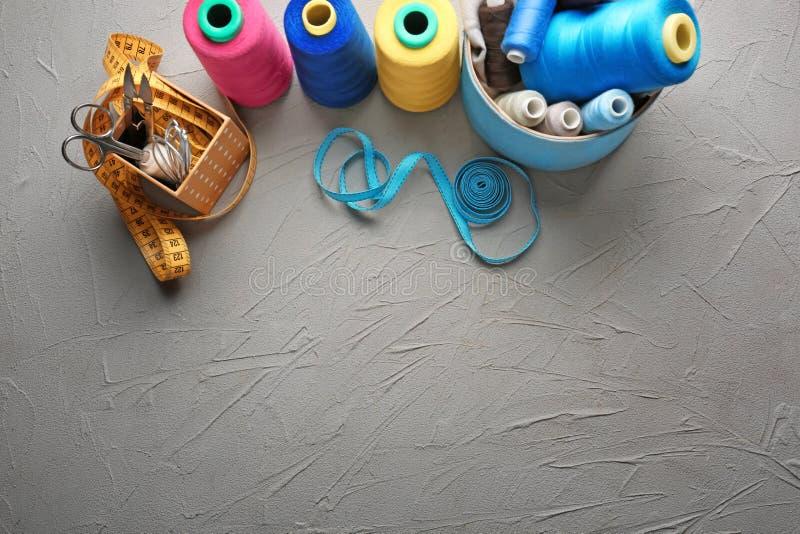 Sammansättning med färgtrådar och sytillbehör på grå texturerad bakgrund royaltyfria foton