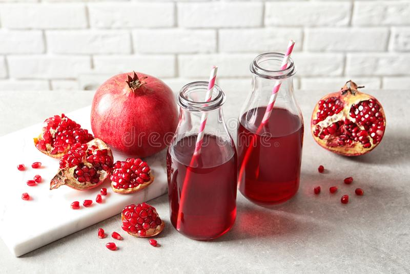Sammansättning med flaskor av ny granatäpplefruktsaft arkivbild
