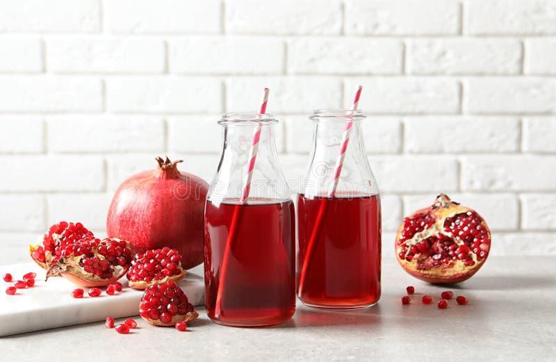 Sammansättning med flaskor av ny granatäpplefruktsaft arkivfoto