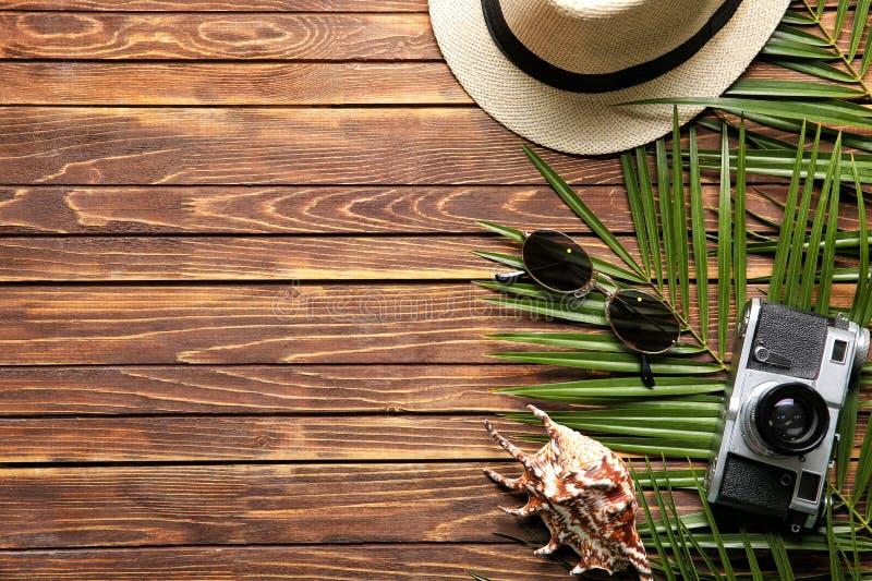 Sammansättning med fotokameran, snäckskalet och sommartillbehör på träbakgrund arkivbilder