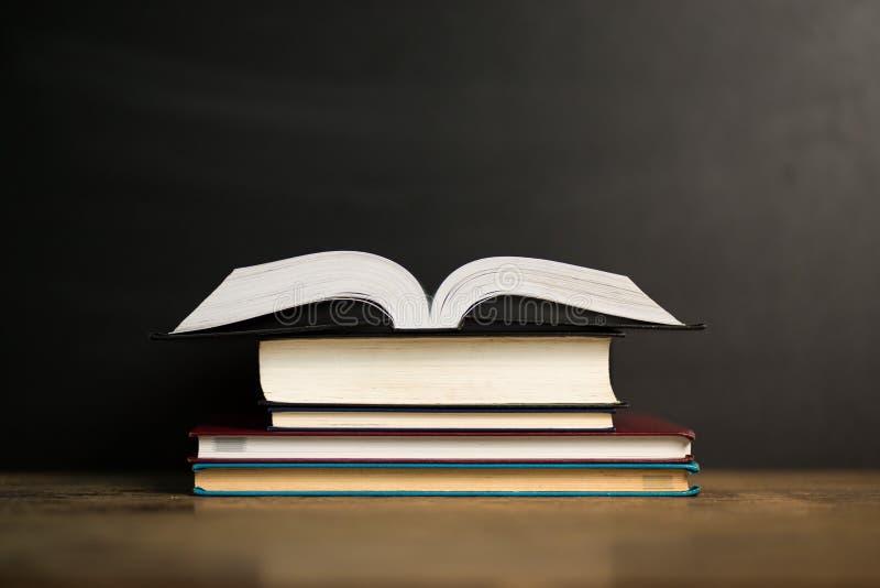 Sammansättning med gamla inbunden bokböcker, dagboken på trädäcktabellen och mörkerbakgrund tillbaka skola till royaltyfri foto