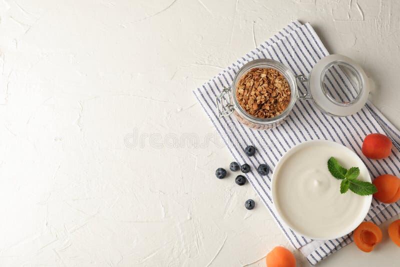 Sammansättning med granola, yoghurt och nya frukter arkivfoton