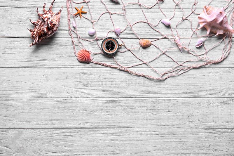 Sammansättning med kompasset, snäckskal och netto på ljus träbakgrund royaltyfri foto