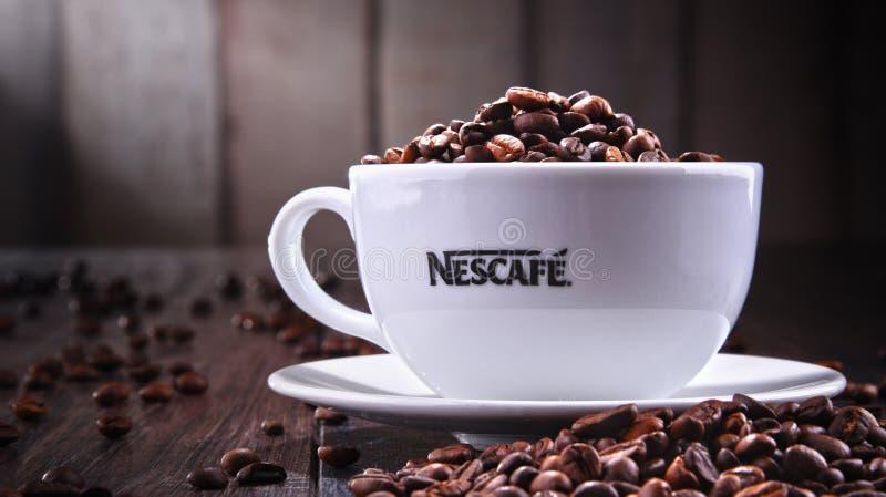 Sammansättning med koppen av Nescafe kaffebönor royaltyfria bilder