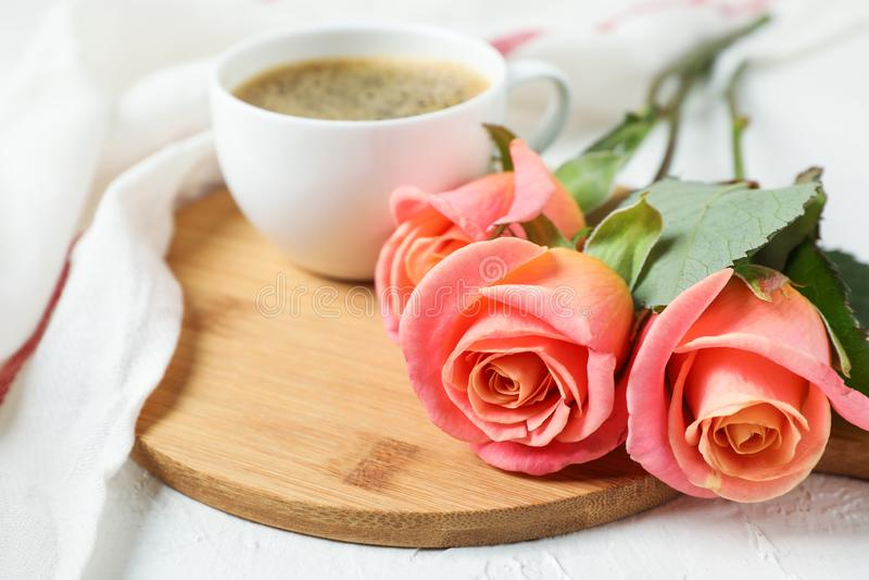 Sammansättning med koppen kaffe, rosor och kökshandduken på vit bakgrund royaltyfri bild