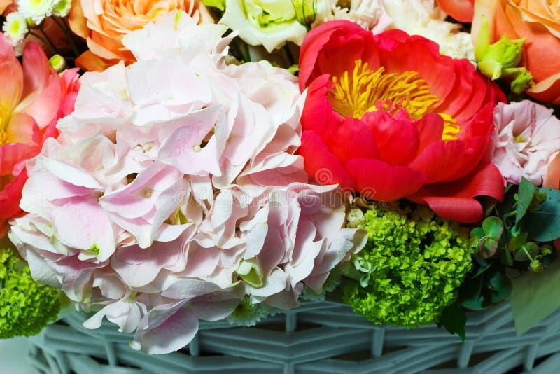 Sammansättning med ljusa färger av pioner, lisianthus, rosor i en vit korg royaltyfria bilder