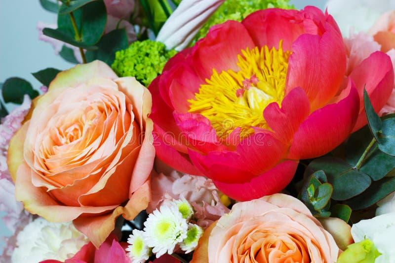 Sammansättning med ljusa färger av pioner, lisianthus, rosor i en vit korg royaltyfri bild