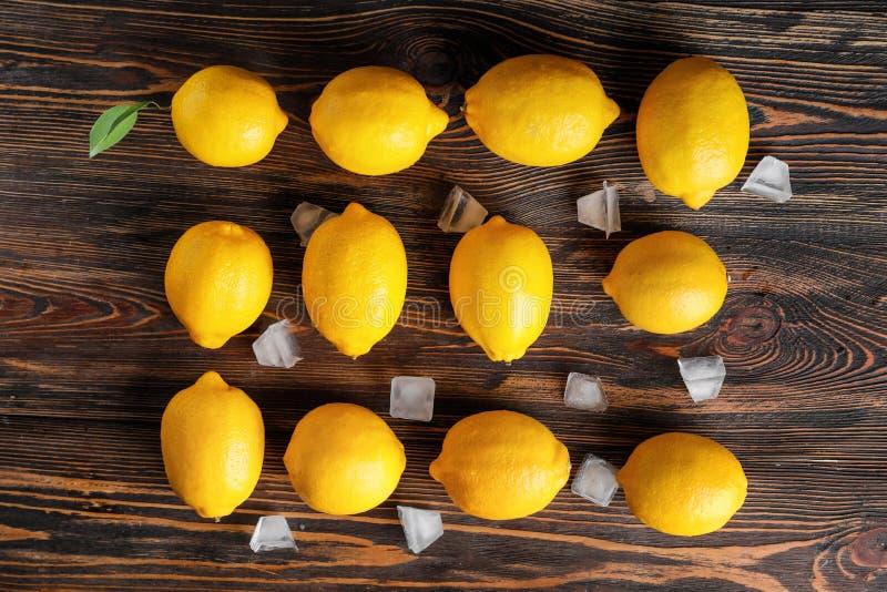 Sammansättning med mogna citroner och iskuber på träbakgrund royaltyfri foto