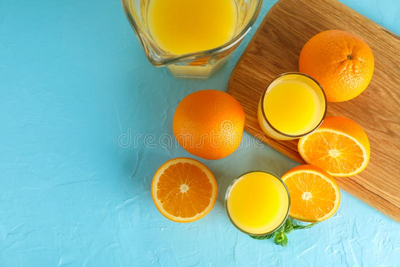 Sammansättning med ny orange fruktsaft i glasföremål, mintkaramell och skärbräda med apelsiner på färgbakgrund, bästa sikt royaltyfri bild