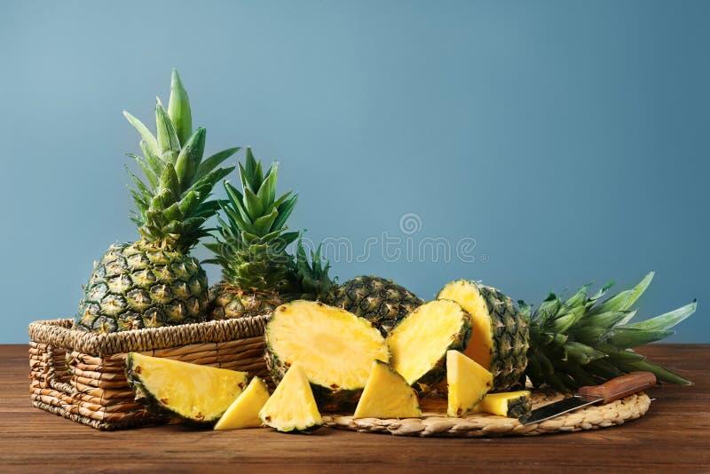 Sammansättning med nya mogna ananors på trätabellen fotografering för bildbyråer