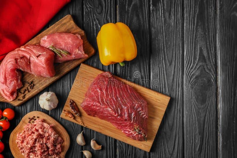 Sammansättning med olika slag av nytt kött på mörk bakgrund royaltyfria bilder