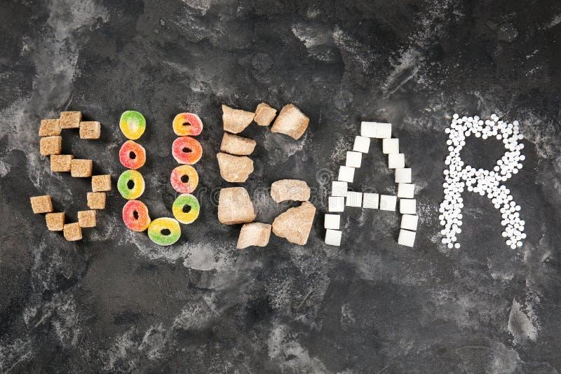 Sammansättning med ordet SOCKER som göras av sötsaker på grå bakgrund royaltyfria foton