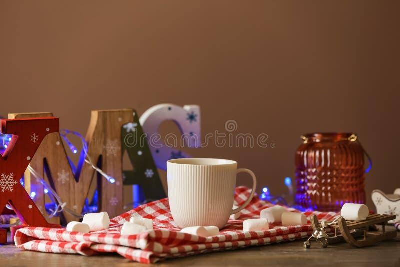 Sammansättning med ordet XMAS gjorde av den träbokstäver och koppen av varm kakao på tabellen arkivfoto