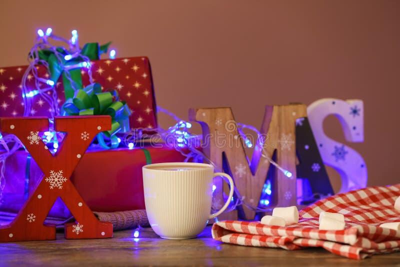 Sammansättning med ordet XMAS gjorde av den träbokstäver och koppen av varm kakao på tabellen royaltyfria bilder