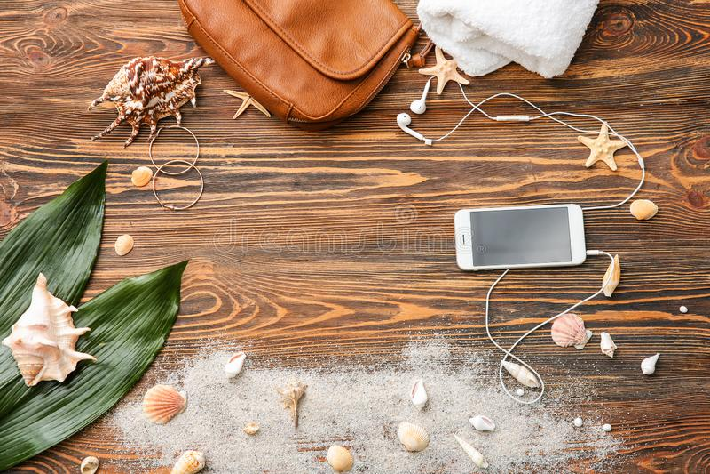 Sammansättning med påsen, smartphonen och snäckskal på träbakgrund arkivbilder