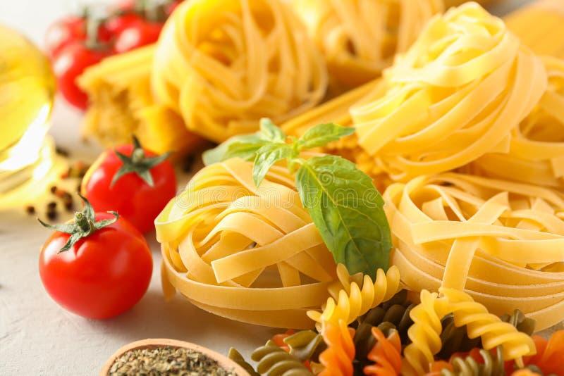 Sammansättning med pasta, tomater, kryddor och olivolja på vit bakgrund royaltyfri bild
