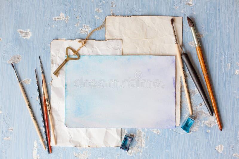 Sammansättning med vattenfärgpapper och målarpenslar på träbakgrund arkivfoto