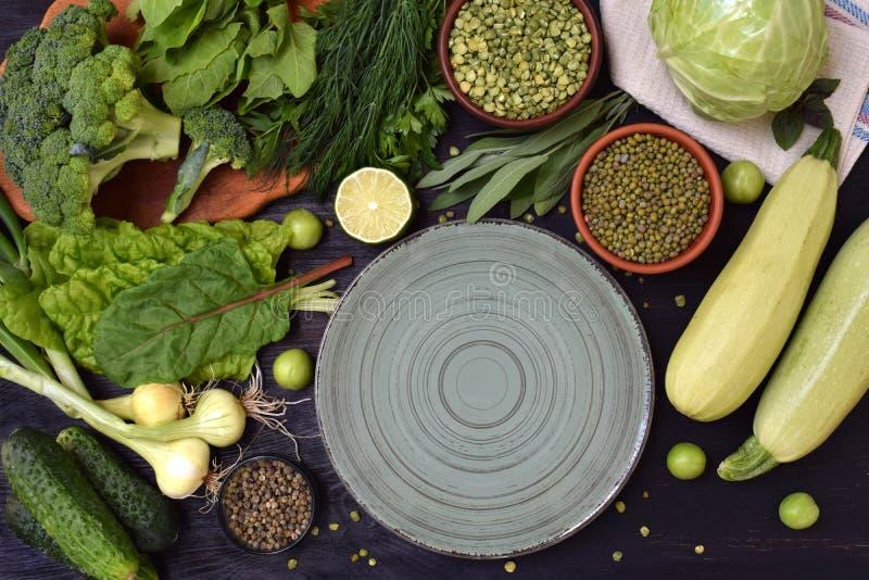 Sammansättning på en mörk bakgrund av gröna organiska vegetariska produkter: gröna lövrika grönsaker, mung bönor, zucchini, vitlö royaltyfria foton