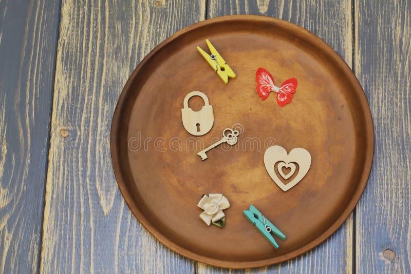 Sammansättning på keramisk maträtt Stiliserad hjärta, lås med tangent, dekorativ fjäril, satängblomma och klädnypor Mörkt naturli arkivbild