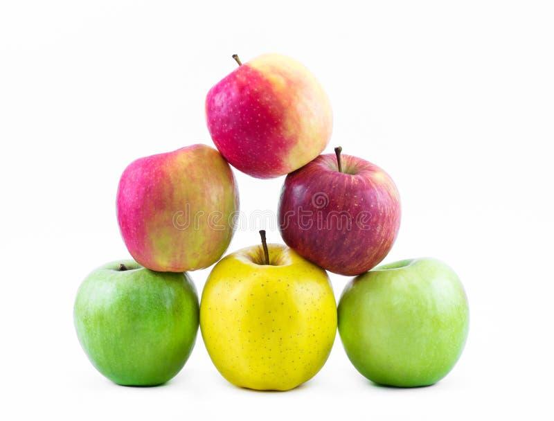 Sammansättning - pyramid av tre typer av äpplen på en vit bakgrund - gräsplan, gult och rött - stilleben royaltyfri fotografi
