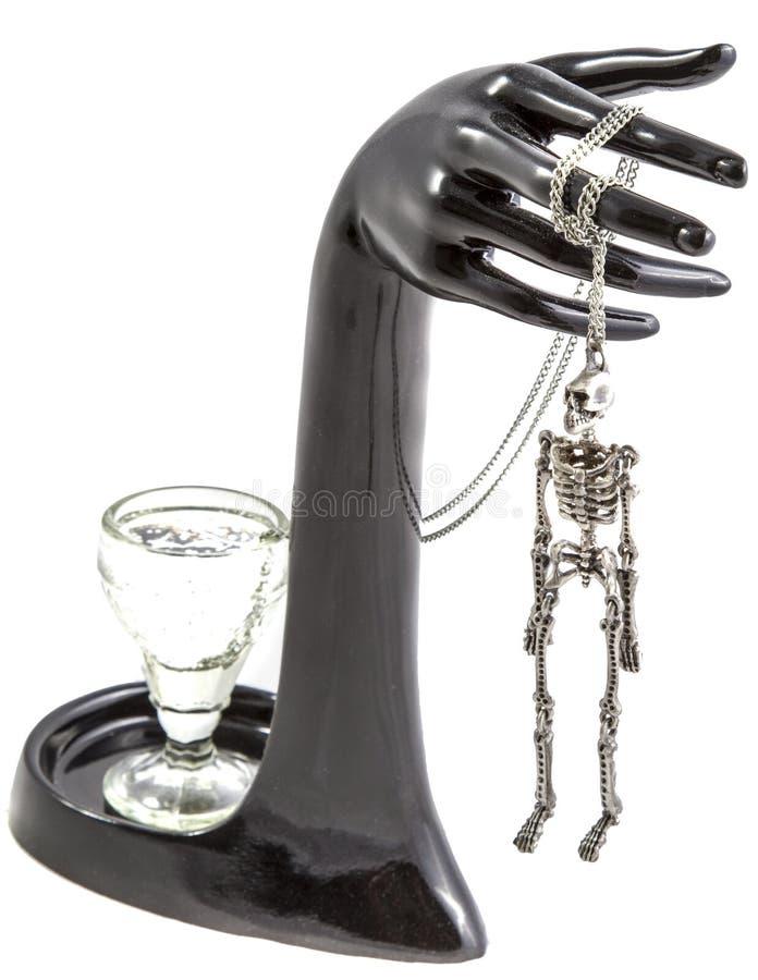 Sammansättningen av ett exponeringsglas, hand och hängt skelettet arkivfoto