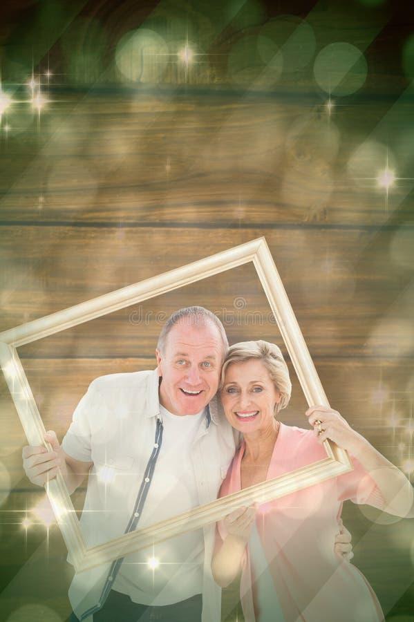 Sammansatt bild av äldre par som ler på kameran till och med bildram arkivfoto