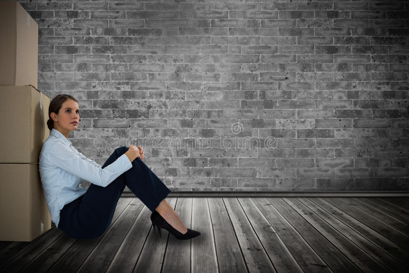 Sammansatt bild av affärskvinnabenägenheten på kartonger mot vit bakgrund royaltyfri bild