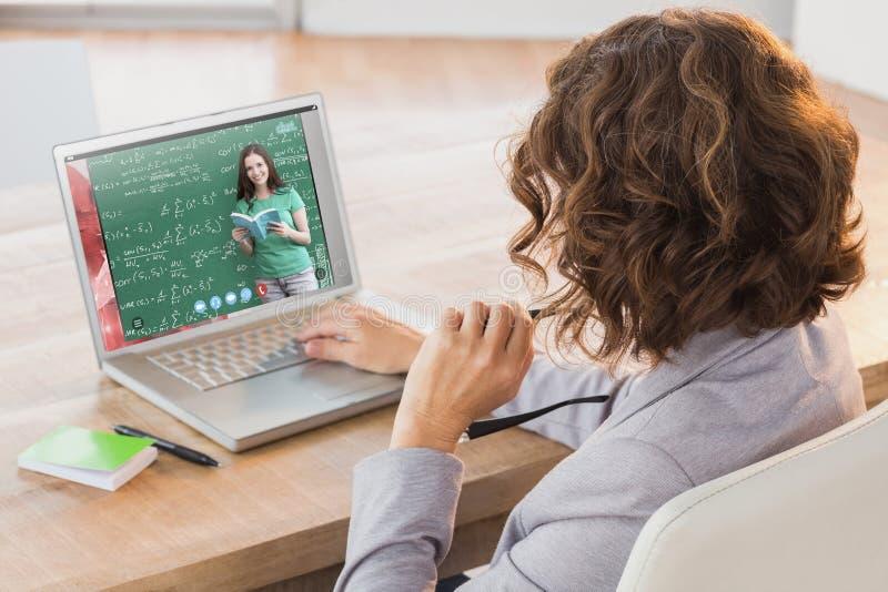 Sammansatt bild av affärskvinnan som använder bärbara datorn på skrivbordet i idérikt kontor royaltyfria foton