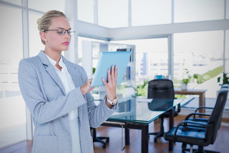Sammansatt bild av affärskvinnan som använder den digitala minnestavlan arkivfoto